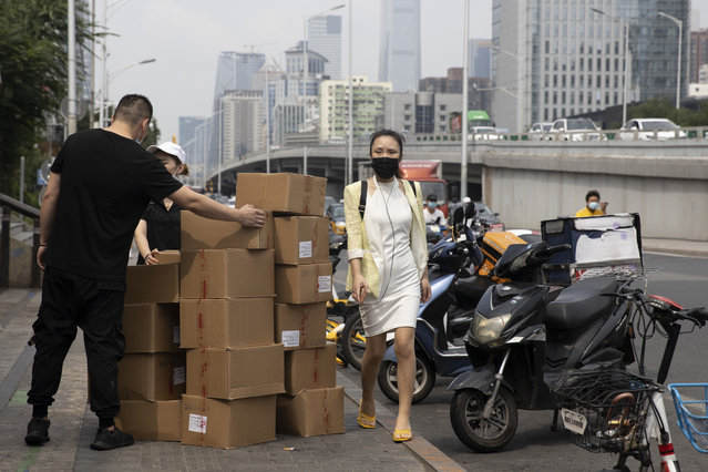 A woman wearing a mask walks past delivery workers moving boxes in Beijing on August 20, 2020. U.S. and Chinese trade envoys discussed strengthening coordination of their government's economic policies during a phone meeting Tuesday, Aug. 25, 2020, the Ministry of Commerce announced. (Photo by Ng Han Guan/AP Photo)