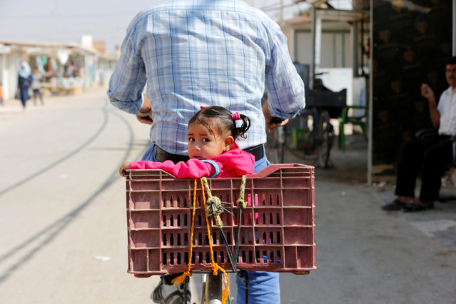 A Syrian refugee rides a bicycle with his daughter at the main market, in the Al-Zaatri refugee camp in the Jordanian city of Mafraq, Jordan, near the border with Syria September 17, 2016. (Photo by Muhammad Hamed/Reuters)