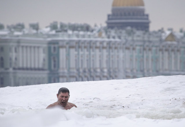 A man swims in a ice hole in the Neva River in St.Petersburg, Russia, Wednesday, January 24, 2018, with the St.Isaac's Cathedral and Winter Palace in the background. The temperature in St. Petersburg is minus 7 degrees Centigrade (19 degrees Fahrenheit). (Photo by Dmitri Lovetsky/AP Photo)