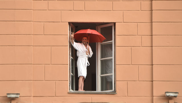 A Belarus opposition supporter raises a V-sign from his window as he welcomes a rally to protest against disputed presidential elections results in Minsk on August 27, 2020. (Photo by Sergei Gapon/AFP Photo)