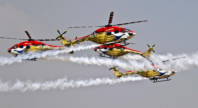 Indian Air Force helicopters cross paths while performing an aerobatic flight on the second day of the Aero India 2013 at Yelahanka air base in Bangalore, India, on February 7, 2013. More than 600 aviation companies along with delegations from 78 countries are participating in the five-day event. (Photo by Aijaz Rahi/Associated Press)