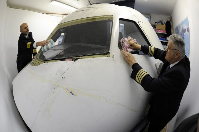 Igor Perne (L), 53, an electronic engineer and a member of the International Virtual Aviation Organisation (IVAO), and fellow virtual pilot Franc Lavric clean the windows of a flight simulator before taking off on a virtual flight in Nova Vas November 13, 2014. (Photo by Srdjan Zivulovic/Reuters)