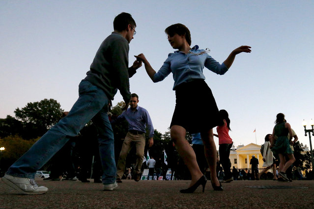 Members of social dance club, Rueda de la Calle DC, perform Cuban salsa dances on Pennsylvania Avenue in front of the White House in Washington, October 15, 2015. The group, which throws dance parties in Washington, chose the White House as their venue Thursday because famed Cuban musical group Orquesta Buena Vista Social Club was performing inside at a reception for the 25th anniversary of the White House Initiative on Educational Excellence for Hispanics. (Photo by Jonathan Ernst/Reuters)
