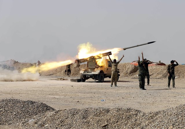 Shi'ite fighters fire a rocket toward Islamic State militants in Baiji, north of Baghdad, October 16, 2015. Iraqi forces and Shi'ite militia fighters recaptured most of the country's largest oil refinery from Islamic State militants on Thursday, security officials said. The report could not be independently confirmed because it is too dangerous for journalists to enter the battle zone around the refinery near the town of Baiji, about 190 km (120 miles) north of Baghdad. (Photo by Thaier Al-Sudani/Reuters)