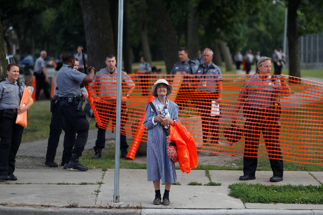 An elderly woman waits for the bus as members of the Milwaukee County Sheriff's department erect a fence around Sherman Park after disturbances following the police shooting of a man in Milwaukee, Wisconsin, U.S. August 15, 2016. (Photo by Aaron P. Bernstein/Reuters)