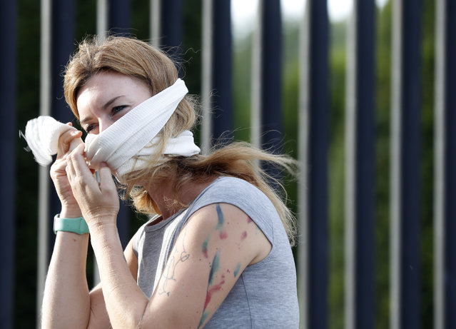 A woman adjusts a bandage in use as a face mask attached to her headphones in Prague, Czech Republic, Saturday, September 19, 2020. The Czech Republic has been been facing the second wave of infections of COVID-19. The number of new confirmed coronavirus infections has been setting new records almost on a daily basis. (Photo by Petr David Josek/AP Photo)