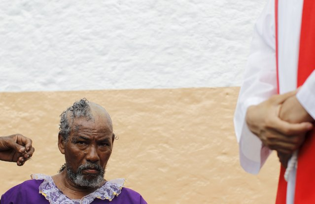 A penitent pilgrim shaves his head outside the local church during the annual celebratory pilgrimage in Portobelo, in the province of Colon October 21, 2015. (Photo by Carlos Jasso/Reuters)