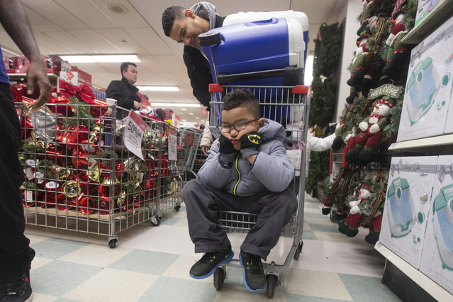 Dylan Morales pouts while shopping with his father Rigoberto, at Kmart on 34th Street, Thursday, November 27, 2014, in New York. Millions of customers are expected to shop on Thanksgiving Day as many retailers remain open on a day traditionally reserved for spending time with family. (Photo by John Minchillo/AP Photo)