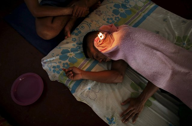 An inmate (L) tends to a fellow prisoner while performing ear candling during an alternative therapy session as part of the ACUDA programme, at a complex of ten prisons in Porto Velho, Rondonia State, Brazil, August 27, 2015. Ear candling, which involves inserting a hollow cone-shaped device into the ear canal and lighting the exposed end, is believed by practitioners to draw out earwax. According to ACUDA the therapy is beneficial for the inmates' emotional health. (Photo by Nacho Doce/Reuters)