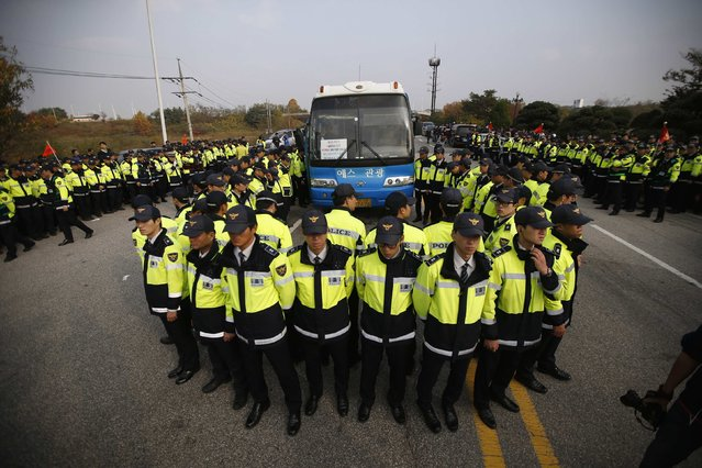 A bus transporting members of an anti-North Korean civic group is surrounded by South Korean policemen near the demilitarised zone separating the two Koreas, in Paju, in this October 25, 2014 file photo. (Photo by Kim Hong-Ji/Reuters)