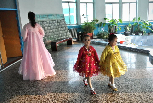 This picture taken on December 15, 2012 shows two girls making their way at a nursery school in the North Korean border town of Siniuju, across from China's northeastern city of Dandong. (Photo by Wang Zhao/AFP Photo)