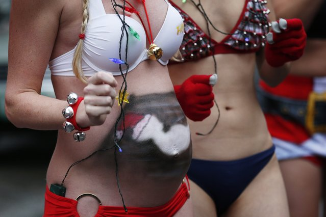 A pregnant woman with a painted stomach participates in the 15th annual Santa Speedo Run through the streets of the Back Bay in Boston, Massachusetts December 6, 2014. (Photo by Brian Snyder/Reuters)