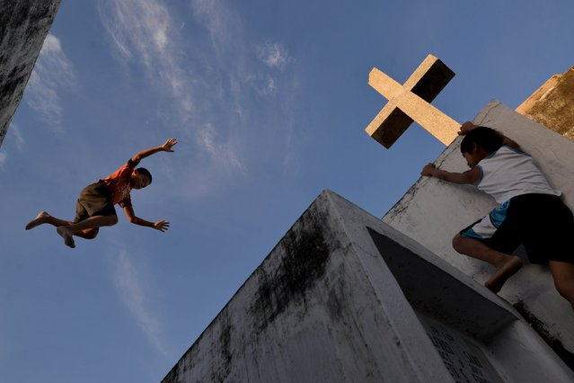 Children play alongside tombs inside the municipal cemetery in Navotas city, north of Manila October 29, 2015. (Photo by Ezra Acayan/Reuters)