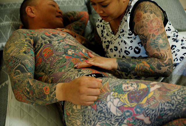 "Bookkeeper Mina Yoshimura, 40, who works at her husband Hiroshi Yoshimura's company, touches a new tattoo that Hiroshi Yoshimura got on the same day, at their home in Tokyo, Japan, October 2, 2020. ""Well, if I had tattoos and he didn't, he'd be able to go places that I couldn't. But since we're both the same, we can go anywhere together. I think that's nice"", said Mina, as she spoke about Hiroshi. (Photo by Kim Kyung-Hoon/Reuters)"
