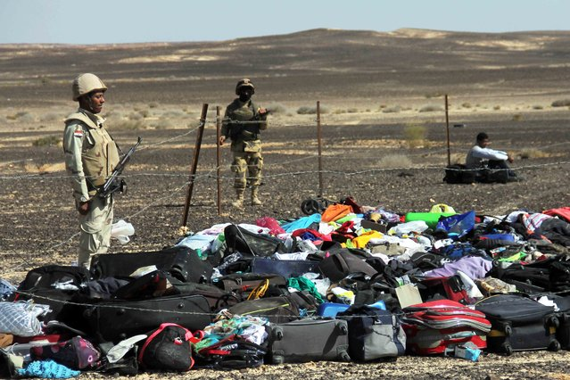 Egyptian Army soldiers stand near luggage and personal effects of passengers a day after a passenger jet bound for St. Petersburg, Russia crashed in Hassana, Egypt, on Sunday, November 1, 2015. The Metrojet plane, bound for St. Petersburg in Russia, crashed 23 minutes after it took off from Egypt's Red Sea resort of Sharm el-Sheikh on Saturday morning. The 224 people on board, all Russian except for four Ukrainians and one Belarusian, died. (Photo by AP Photo)