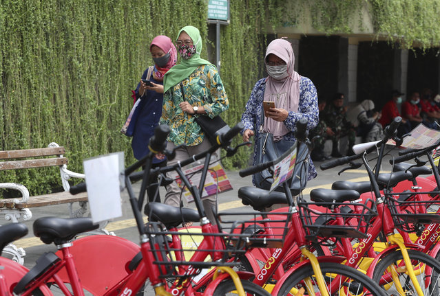 Indonesian women wearing masks as a precaution against the coronavirus outbreak walk on a pedestrian street in Jakarta Monday, October 12, 2020. (Photo by Achmad Ibrahim/AP Photo)