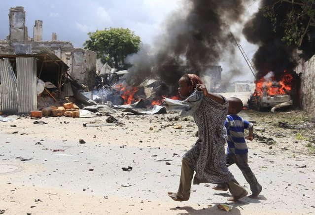 A Somali girl and her brother run to safety near the scene of a blast in Mogadishu April 14, 2013. At least 16 people were killed as two car bombs exploded outside the law courts in Somalia's capital Mogadishu and gunmen stormed the building on Sunday, before a gunbattle erupted with security forces besieging the compound, witnesses said. (Photo by Feisal Omar/Reuters)