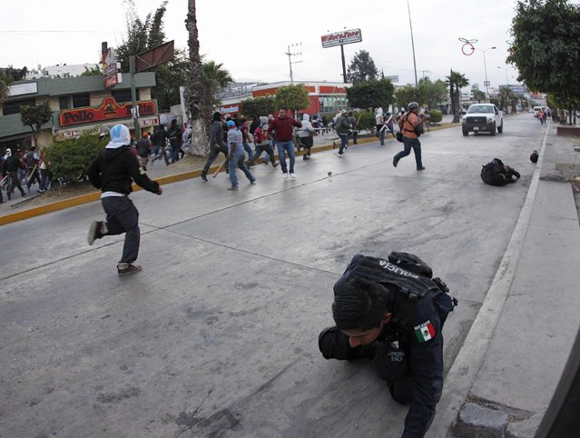An injured federal police officer (bottom R) is seen as people chase after a car which reversed away after running over civilians, federal police officers, and journalists, during clashes in Chilpancingo, Guerrero, December 14, 2014. (Photo by Jorge Dan Lopez/Reuters)