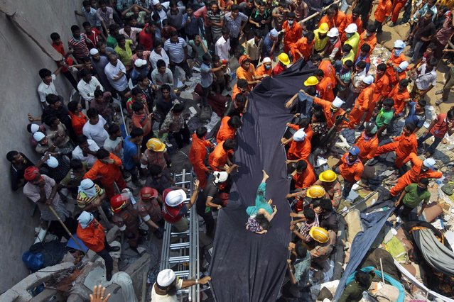 Bangladeshi people watch as rescuers use a piece of fabric to lower the body of a woman after she was discovered inside a building that collapsed Wednesday in Savar, near Dhaka, Bangladesh,Thursday, April 25, 2013. By Thursday, the death toll reached at least 194 people as rescuers continued to search for injured and missing, after a huge section of an eight-story building that housed several garment factories splintered into a pile of concrete. (Photo by A. M. Ahad/AP Photo)