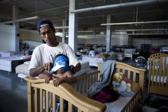 In this Thursday, August 27, 2015 photo, Aitnes Kenan dresses his 1-year-old son, Tiason, at the Institute for Human Services, a homeless shelter and comprehensive social services agency, in Honolulu. While there are shelters and programs to help the homeless, there aren't enough empty beds to meet the needs of an estimated 7,620 people who live on the streets, primarily concentrated on the main island of Oahu. (Photo by Jae C. Hong/AP Photo)