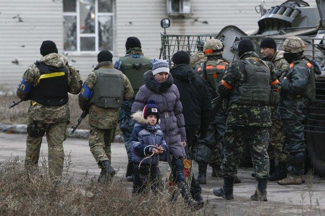 A woman with a child walks past Ukrainian servicemen in the eastern Ukrainian town of Debaltseve in Donetsk region, December 24, 2014. (Photo by Valentyn Ogirenko/Reuters)