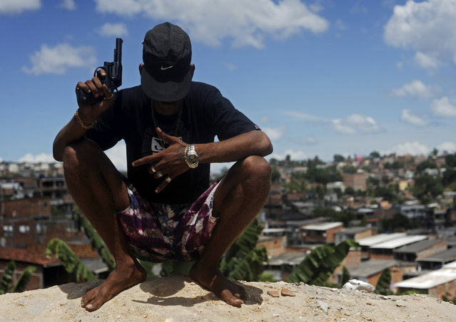 A Brazilian drug gang member nicknamed Firecracker, 22, poses with a gun atop a hill overlooking a slum in Salvador, Bahia State, April 11, 2013. One of Brazil's main tourist destinations and a 2014 World Cup host city, Salvador suffers from an unprecedented wave of violence with an increase of over 250% in the murder rate, according to the Brazilian Center for Latin American Studies (CEBELA). (Photo by Lunae Parracho/Reuters)