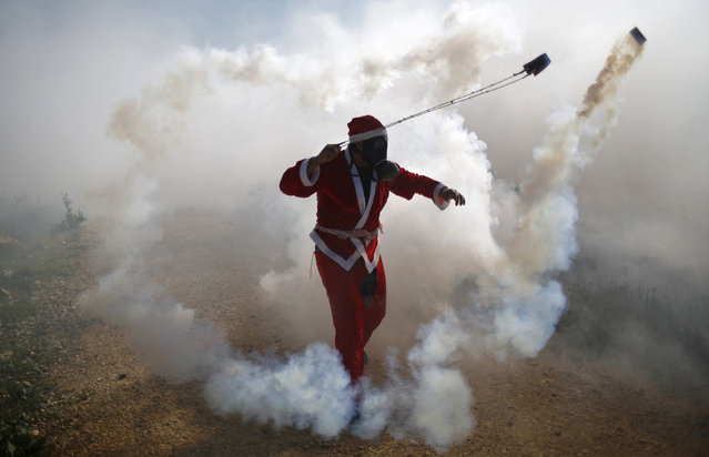 A Palestinian protester, dressed as Santa Claus, uses a slingshot to return a tear gas canister fired by Israeli troops during clashes following a demonstration against Jewish settlements in the West Bank village of Bilin, near Ramallah December 26, 2014. (Photo by Mohamad Torokman/Reuters)
