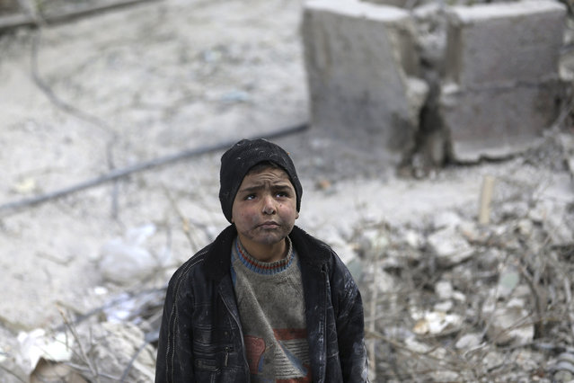 A boy looks at damage of a collapsed building after what activists said was was an air strike by forces loyal to Syria's President Bashar al-Assad in the Duma neighborhood of Damascus, December 21, 2014. (Photo by Bassam Khabieh/Reuters)