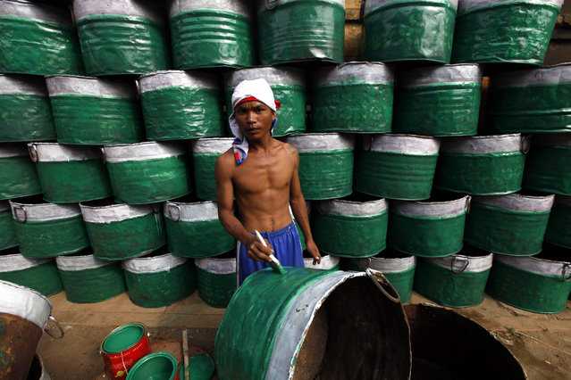 A worker paints an old barrel at a workshop in Mandalay, Myanmar, 10 November 2015. (Photo by Hein Htet/EPA)