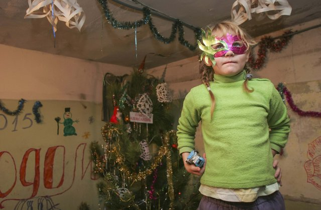A girl plays in a basement with festive decorations used as a bombshelter in Donetsk December 30, 2014. (Photo by Igor Tkachenko/Reuters)