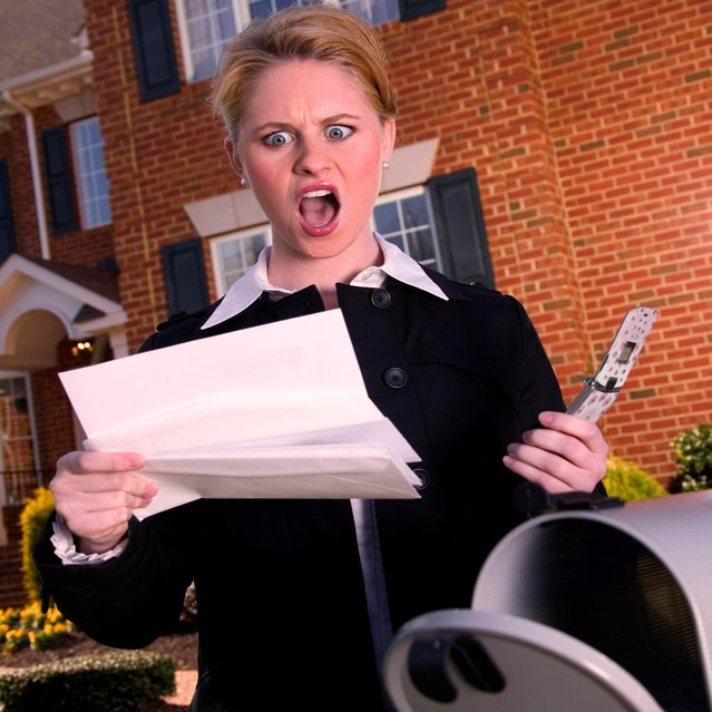 Angry woman reading mail at mailbox. (Photo by Christopher Winton-Stahle/Getty Images)