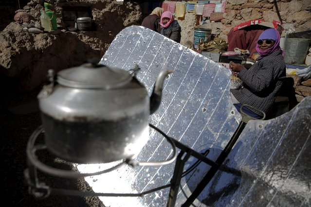Tibetan women sit behind a solar cooker in front of small house at Namtso lake in the Tibet Autonomous Region, China November 18, 2015. (Photo by Damir Sagolj/Reuters)