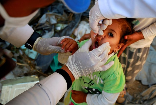 A girl receives a polio vaccine during a three-day immunization campaign in Sanaa, Yemen on November 29, 2020. (Photo by Nusaibah Almuaalemi/Reuters)