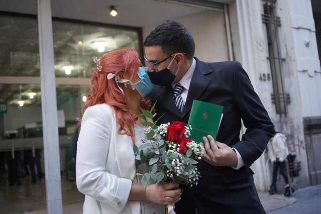Newlyweds Laura Gomez (L) and Martin Larzabal kiss while wearing face masks after getting married at a civil status registration office amid the outbreak of the coronavirus disease (COVID-19), in Montevideo, Uruguay on May 8, 2020. (Photo by Mariana Greif/Reuters)