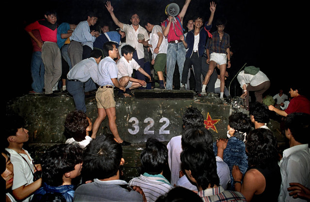Chinese student protestors swarm over a captured PLA tank, Tiananmen Square Protests, Beijing, China, 1989. (Photo by Jeff Widener/Associated Press)