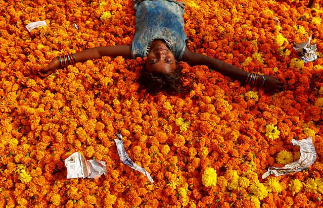 A girl plays on a pile of discarded flowers outside a market, the day after the Diwali celebrations in Mumbai, India October 31, 2016. (Photo by Shailesh Andrade/Reuters)