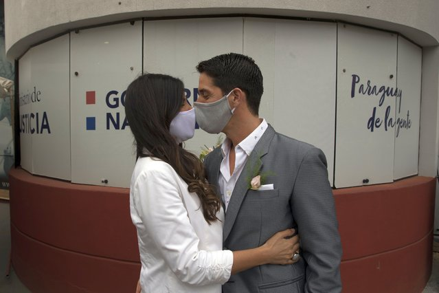 """Bride Loris Sanchez and groom Manuel Soria, wearing protective face masks as a precaution against the spread of the new coronavirus, share a kiss before during their wedding ceremony at the Civil Registry office, in Asuncion, Paraguay, Saturday, June 13, 2020. The government has eased restrictive quarantine measures due to the COVID-19 pandemic, authorizing the opening of some stores, restaurants and government offices that had been closed since March 10, as part of a plan coined, """"Intelligent Quarantine"""". (Photo by Jorge Saenz/AP Photo)"""