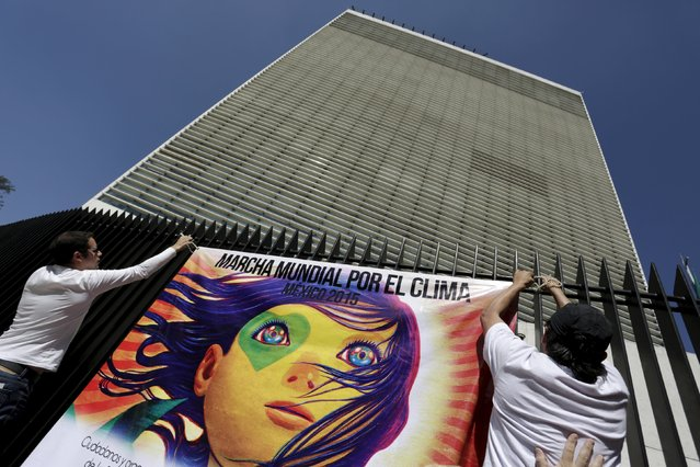 """Protesters place a banner on a fence in the perimeter of the Senate building as they take part in a rally held the day before the start of the 2015 Paris Climate Change Conference (COP21), in Mexico City, Mexico November 29, 2015. The banner reads, """"Global climate march-Mexico 2015"""". (Photo by Daniel Becerril/Reuters)"""