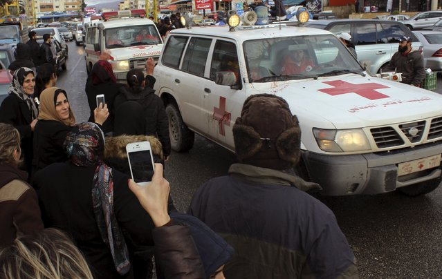 People take pictures of a convoy of Red Cross vehicles carrying the newly released Lebanese soldiers and policemen who were captured by the al Qaeda-linked Nusra Front in Arsal, as they drive in Baalbek, in the Bekaa valley, Lebanon December 1, 2015. (Photo by Ahmad Shalha/Reuters)