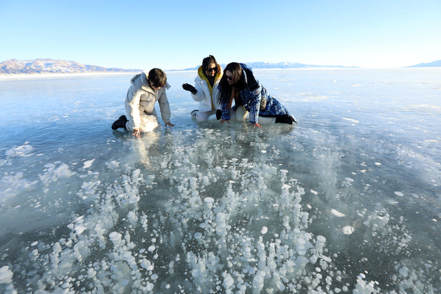 Women observe bubbles frozen under the surface of Sayram lake in Bortala, Xinjiang, China on January 18, 2021. (Photo by Top Photo Corporation/Rex Features/Shutterstock)