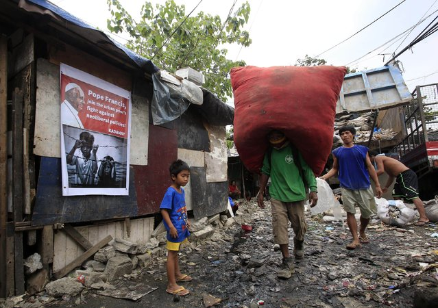 A man carrying bags of used plastic passes by a poster addressed to Pope Francis at a slum area in Quezon city, metro Manila January 13, 2015. (Photo by Romeo Ranoco/Reuters)