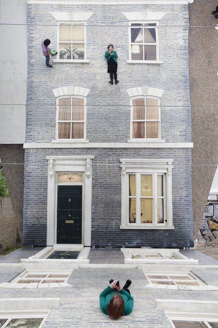 "A woman appears in a large-scale installation art piece by Leandro Erlich, named ""Dalston House"", on June 24, 2013 in London, England. Part of the ""Beyond Barbican"" summer series of events, the interactive installation is a full facade of a late nineteenth-century Victorian terraced house built on the ground with a large mirror above it to reflect people as to appear dangling from the structure.  (Photo by Dan Dennison/Getty Images)"