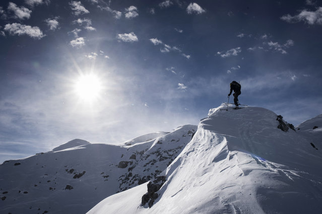 A backcountry skiier climbs up towards the Mederger Flue peak (2706 meters above sea level), on Monday, January 12, 2015, in Davos, Switzerland. (Photo by Gian Ehrenzeller/AP Photo/Keystone)