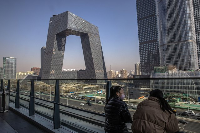 Women stand on an observation deck overlooking the China Central Television (CCTV) building (C) in the Central Business District (CBD) area of Beijing, China, 05 February 2021. Britain's media regulator Ofcom revoked China's state-owned broadcaster CGTN license in the UK, according to media reports. CGTN (China Global Television Network), based in Beijing, is owned by the China Central Television, a state-owned broadcaster. CGTN formerly known as CCTV-9 and CCTV News, is an international English-language news channel. (Photo by Roman Pilipey/EPA/EFE)