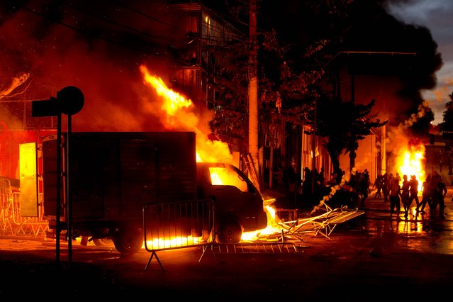 Protesters, right, set cars and stores on fire  during a demonstration in Belo Horizonte, Brazil, Wednesday, June 26, 2013. Brazilian anti-government protesters in part angered by the billions spent in World Cup preparations and police clashed Wednesday near the stadium hosting a Confederations Cup football match, with tens of thousands of demonstrators trying to march on the site confronting police firing tear gas and rubber bullets. (Photo by Victor R. Caivano/AP Photo)