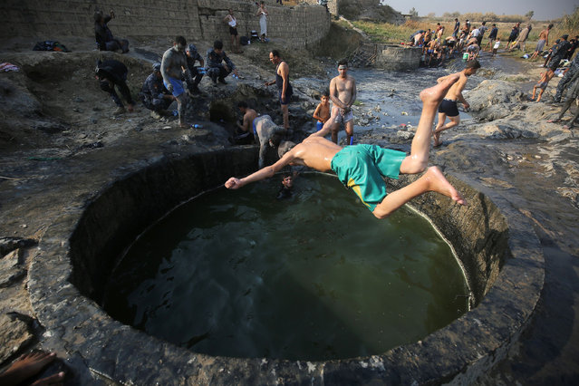 Iraqis and Iraqi forces members bathe in a sulphur pond in the Hamam al- Alil area, about 14 kilometres from the southern outskirts of Mosul, on November 7, 2016, after recapturing it from Islamic State (IS) group jihadists during the ongoing operation to regain control of the city of Mosul from the group. (Photo by Ahmad Al-Rubaye/AFP Photo)