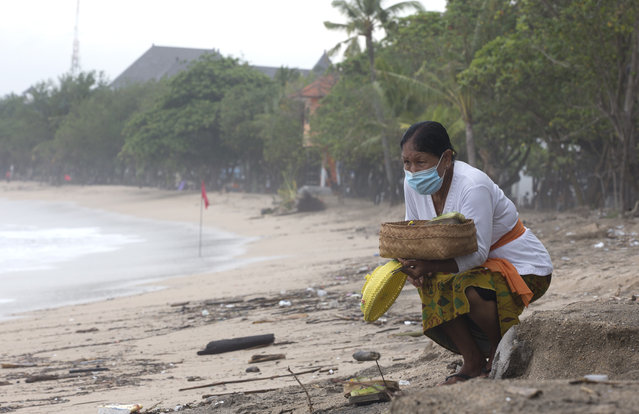 A Balinese woman gives an offering to Hindu god in Bali, Indonesia on Wednesday, February 3, 2021. Airlines and hotels are desperately holding out for a recovery in travel. But instead they're seeing more restrictions, from Canada to Indonesia. Governments are extra cautious due to the new, more contagious variants of the coronavirus. (Photo by Firdia Lisnawati/AP Photo)