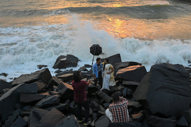 A couple gets photographed at the sea front during sunrise in Pondicherry on February 9, 2021. (Photo by Punit Paranjpe/AFP Photo)