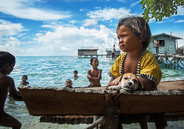 """""""The beach alone children"""". No nationality of Malaysia """"Bawo – Rotter"""" children, with sadness alone on the beach, watching the kids in the game. Location: Malaysia, Semporna. (Photo and caption by He Yuanquan/National Geographic Traveler Photo Contest)"""