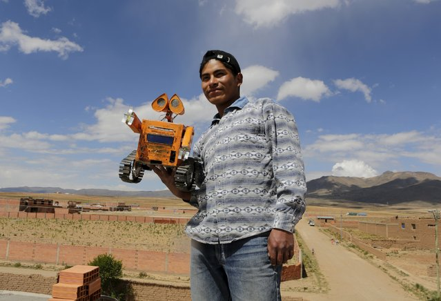 Bolivian student Esteban Quispe, 17, holds a replica of the Wall-E character in Patacamaya, south of La Paz, December 10, 2015. (Photo by David Mercado/Reuters)